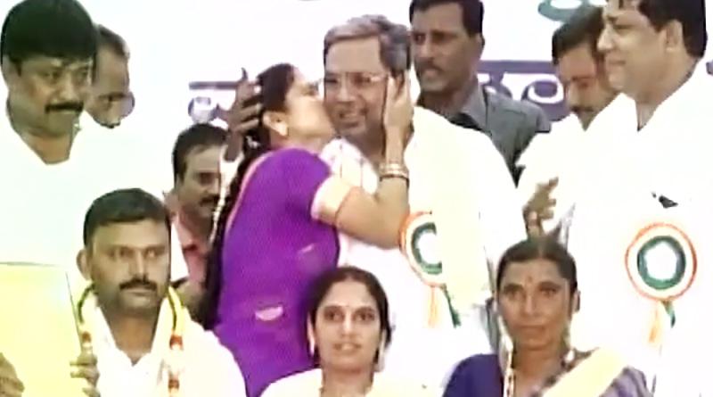A woman kisses Karnataka CM Siddaramaiah during a state-level program