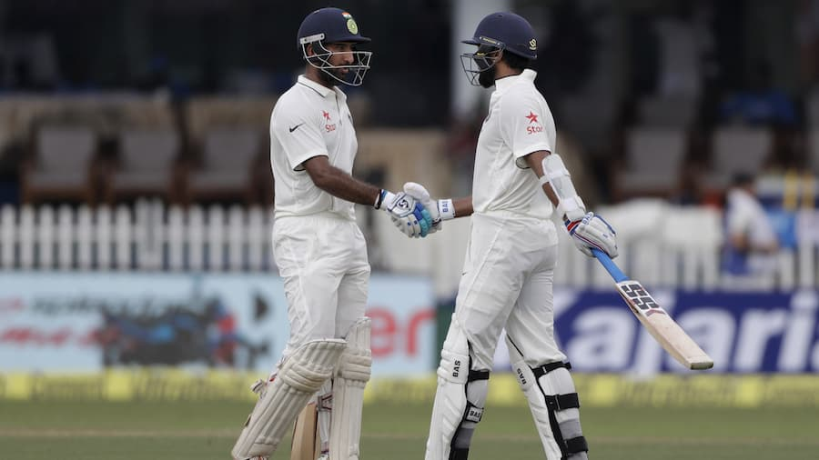 India's Cheteshwar Pujara, right, shakes hand with Murali Vijay after Vijay made half century against New Zealand during their first test match in Kanpur, India , Thursday, Sept. 22, 2016. (AP Photo/ Tsering Topgyal)