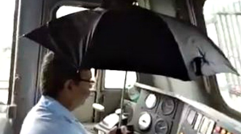 Pilot Of A Running Train Drives With One Hand; Holds Umbrella In Another