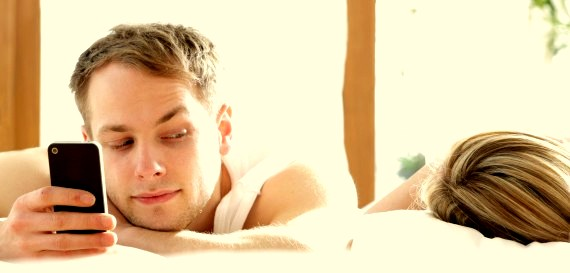 Man with phone in bed, looking at woman asleep