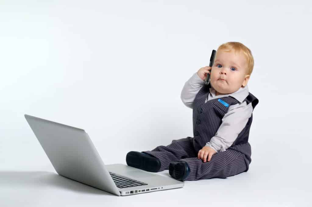 blond baby in suit working with laptop