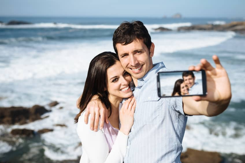 Young couple on honeymoon travel in Asturias coast, Spain, taking selfie portrait photo with smartphone camera.