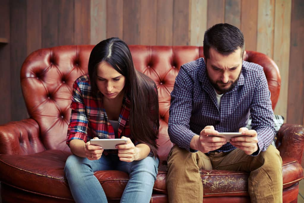 54207353 - concept photo of smartphone addiction. young woman and man sitting on the sofa with smartphone and do not looking at each other
