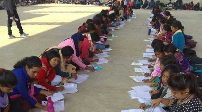Students sit in the open for exams