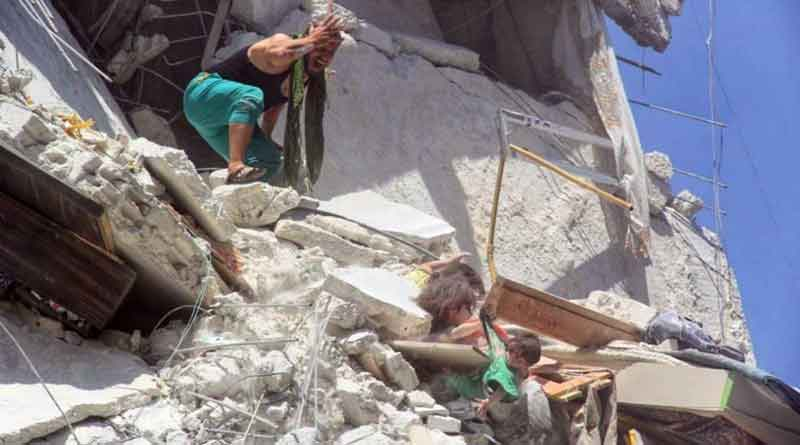 Sister grabbing baby dangling from bombed building in Syria