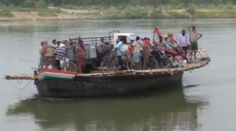 Gathering of people into a boat at Katwa ferry point, police makes them deborad