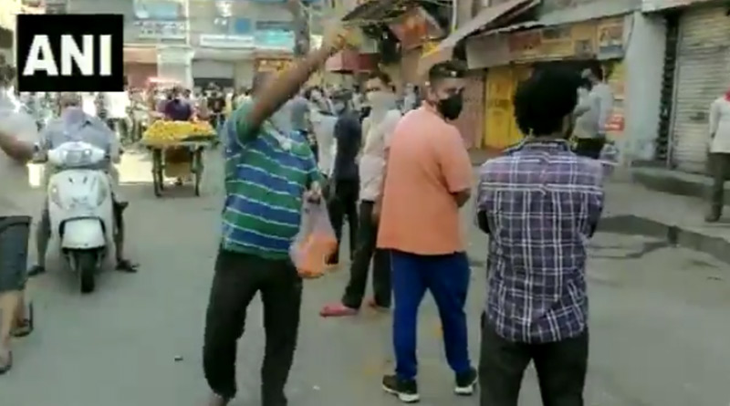 Man showers petals on people standing in queue outside liquor shops